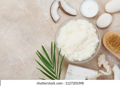 Body scrub of coconut oil, sugar and shavings in glass jar on stone table top view. Homemade cosmetic for peeling and spa care. Flat lay.