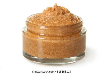 Body scrub of ground coffee and sugar in jar on white isolated background. Homemade cosmetic for peeling and spa care.