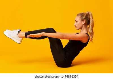 Body Shaping Workout. Girl Doing Abs Exercise With Leg Raise On Yellow Studio Background.