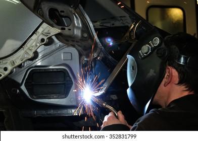 Body shop worker welding car panel.