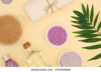 Body skin care spa background. Sea salt scrub, dry massage brush, body oil. Body care, skin tightening, relaxation. Yellow background. Flat lay, top view