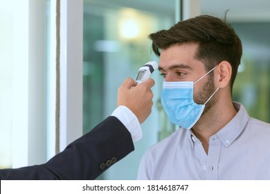 Body temperature check, Receptionist and guest wearing face mask at front desk  at hotel. Covid 19 and coronavirus infection protection and protective policy concept