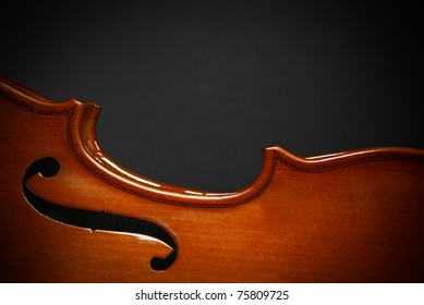 Body of a Violin, in the spotlight, isolated with a dark grey background.