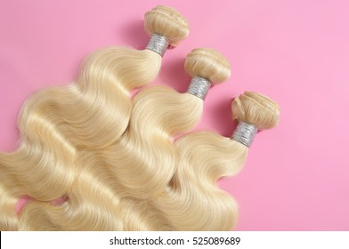 body wave blonde  human hair extensions on pink background