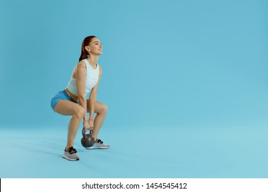 Body workout. Fitness woman in sports wear exercising squats with gym weights at studio. Full length portrait of fit girl doing squat exercise with kettlebell on blue background