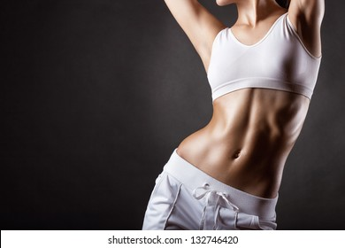 The body of a young athletic girl on a dark background