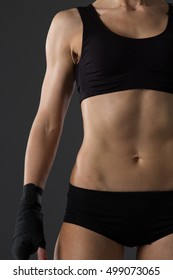 The body of a young athletic girl on dark background.