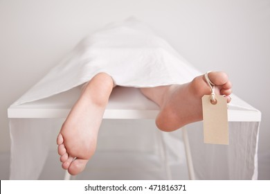 Body of a young boy on a mortuary slab with his bare feet sticking from under the sheet covering him with a blank tag hanging from the toe for identification