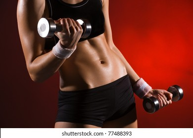Body of a young fit woman lifting dumbell. Shot in studio on a red background.