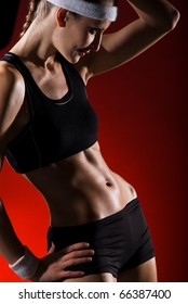 Body of a young fit woman. Shot in studio on a red background.