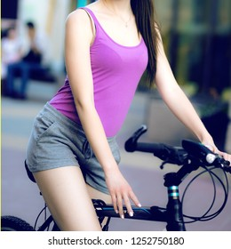 the body of a young girl in sportswear on a Bicycle in the background of the city