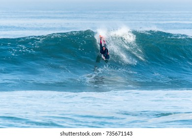 Bodyboarder surfing ocean wave on a sunny day.