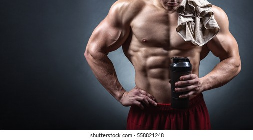 Bodybuilder after a workout with a shaker on a dark background