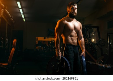 bodybuilder with beard in the gym exercising barbell