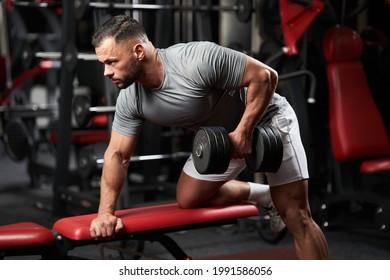 Bodybuilder faisant du haltère pour faire de l'exercice sur banc dans la salle de fitness