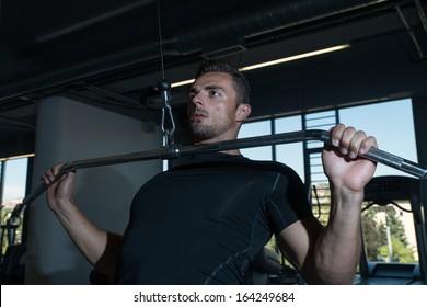 Bodybuilder Doing Heavy Weight Exercise For Back. Lat Pull down Heavy Weight Exercise For Back