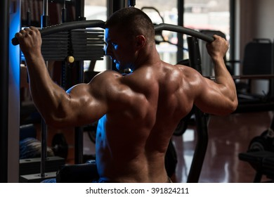 Bodybuilder Doing Heavy Weight Exercise For Back On Machine In Gym