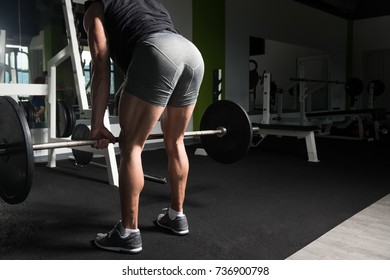 Bodybuilder Doing Heavy Weight Exercise For Back With Barbell In Modern Gym