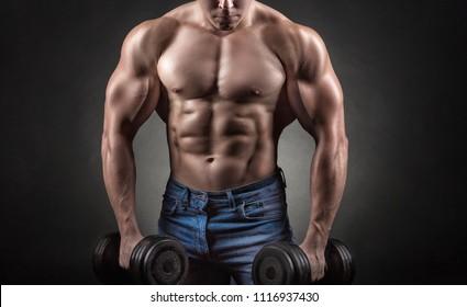 Bodybuilder. Fit muscular bodybuilder man exercising with dumbbell against a black background