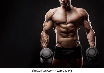 Bodybuilder. Fit muscular bodybuilder man exercising with dumbbell against a black background. Studio shot