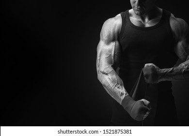 Bodybuilder fitness lifestyle concept Croped black and white shot on black background Man is wrapping hands with boxing wraps isolated Strong hands and fist, ready for training and active exercise