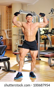 Bodybuilder flexing his muscles in gym and smiling