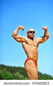 Bodybuilder flexing his muscles outdoors