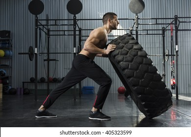 Bodybuilder flipping tire at the gym
