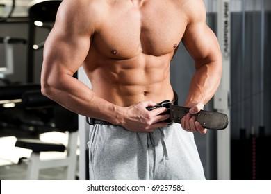bodybuilder girding on his bodybuilding belt
