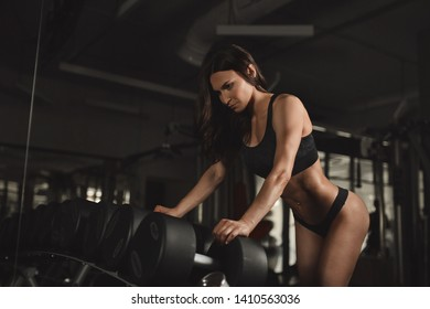 Bodybuilder Girl in a gym working out, lifting weights.