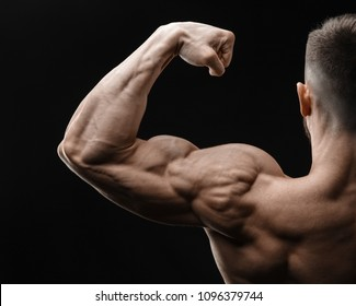 Bodybuilder in good shape against a dark background. Man posing, showing his muscle definition.