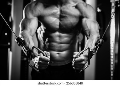 bodybuilder guy in gym pumping up hands close up. Black and white