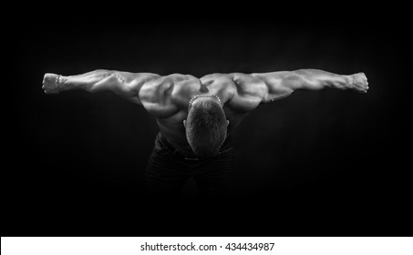 Bodybuilder hand in parties on the black background