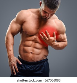 Bodybuilder with heart pain over gray background. Concept with highlighted glowing red spot.