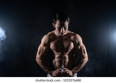 Bodybuilder holding big syringe. concept of steroid in the sport and addiction