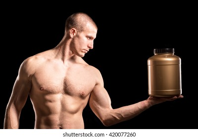 Bodybuilder holding a brown plastic jar whey protein with his hand isolated on dark background