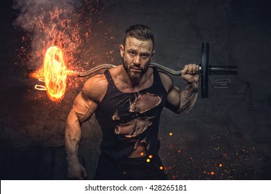 Bodybuilder holds burning barbell on his shoulder.