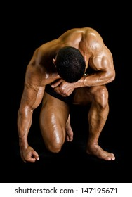 Bodybuilder kneeling with head down - isolated on black