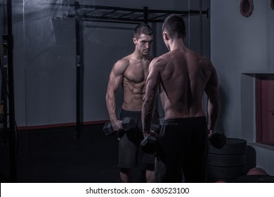 bodybuilder, looking at himself, holding dumbbells, dark indoors gym