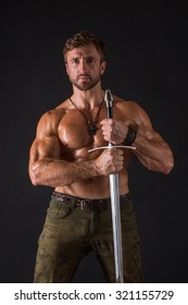 Bodybuilder man holding a sword in front of him. Short-haired man in jeans looking at the camera isolated on black background.