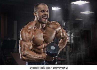 Bodybuilder man lying exercisers squeezing large dumbbells.