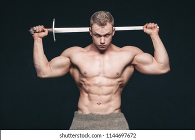Bodybuilder man posing with a sword isolated on black background. Serious shirtless man demonstrating his mascular body