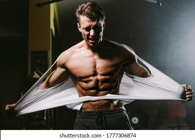 Bodybuilder man ripping shirt and showing his muscular body torso with abs. Hot and handsome man tearing shirt with anger and furious. Fitness motivation background