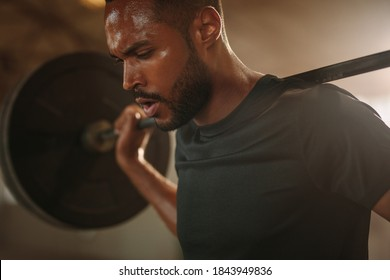 Bodybuilder man working out at gym with heavy weights. Fitness man doing back squats with barbell.