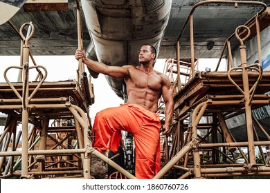 Bodybuilder mechanic in orange uniform with naked torso poses under abandoned airplane's wing in daytime.