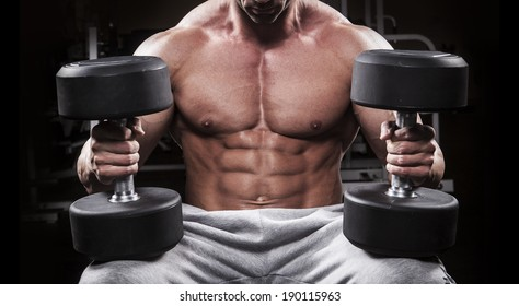 Bodybuilder men training at the gym with dumbbell