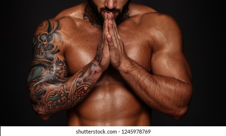 Bodybuilder with muscle torso. Banner image of sexy man with muscular body. Portrait of sexi male model. Hot macho in prayerful pose with folded hands on black background. 16 in 9 crop for design.