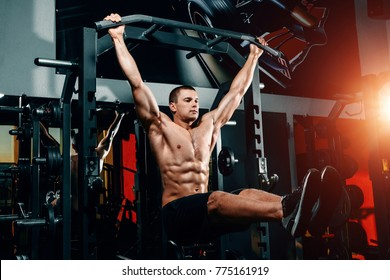 bodybuilder on the bar raises his legs up, exercises on the press in the gym. Great training of a professional bodybuilder.