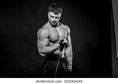 A bodybuilder performs fitness exercises in the studio. Black and white. Healthy lifestyle.