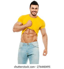 Bodybuilder or personal trainer pulling his t-shirt up and smiling at the camera on white background